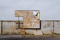 Kaputte Plakatwand an einer häßlichen Mauer