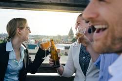 Junge Business Leute auf Dachterrasse beim Afterwork Beer