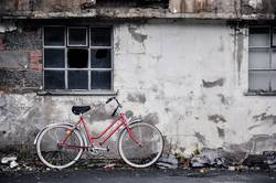 Rotes Fahrrad, graue Wand. Trist und kaputt.