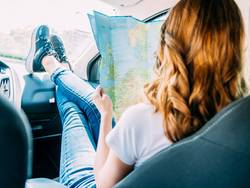 Young Woman Getting Ready To Travel By Car And Looking At Map