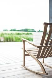 Schaukelstuhl auf Veranda mit Blick ins Grüne