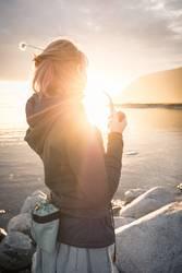 Junge Frau mit Pfeife in der Mitternachtssonne am Polarmeer