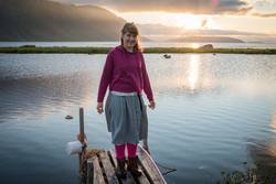 Junge Frau auf kleinem Holzsteg. Fjord. Mitternachtssonne