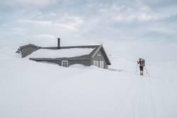 Skifahrer erreicht tief verschneite Hütte