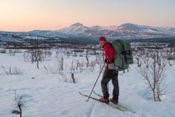 Winterlicher Abenteurer in Abendstimmung vor Berglandschaft