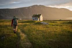 Wanderer erreicht Hütte in abendlicher Sonnenflut