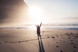 Junge Frau grüßt am Strand im Sonnenlicht am Nordmeer