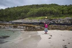 Strandszene - Junge Frau wirft gelben Ball