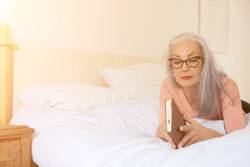 Mature woman reading book while lying on bed