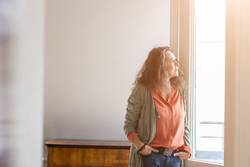 Middle-aged woman staring out of a window