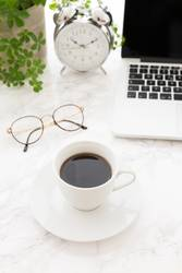 Cup of coffee, laptop, glasses and alarm clock