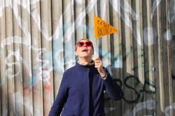 Frau im Mantel mit Brille und Wimpel vor Graffitiwand aus Beton