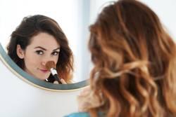 junge Frau pudert Nase im Spiegel