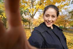 happy young woman taking selfie in autumn