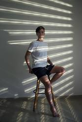 Junge Frau sitzt auf einem Hocker in Lichtstreifen beleuchtet