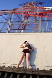 Junge Frau steht unter rot-weißem Freileitungsmasten