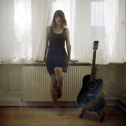 Junge Frau sitzt am Fenster neben Gitarre