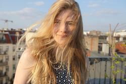 Blondes Mädchen mit wehendem Haar auf einer Dachterrasse