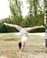 Tättowierte Frau macht Handstand/Spagat an einer Birke