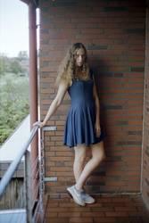 Junge Frau steht auf einem Balkon von Ziegelsteinmauer
