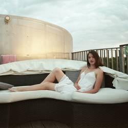 Portrait einer jungen Frau auf einem Sofa einer Dachterrasse