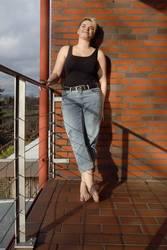 Junge Frau auf sonnigem Balkon