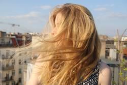 Blondes Mädchen mit wehendem Haar auf Dachterrasse