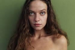 Portrait einer jungen Frau vor grüner Wand