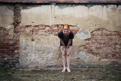 Portrait einer jungen Frau vor einer alten Ziegelsteinmauer