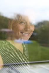 Portrait einer jungen Frau hinter einem Fenster