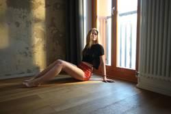 Blondes Mädchen sitzt vor einem Fenster auf dem Boden