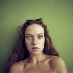 Rechteckiges Portrait einer jungen Frau vor grüner Wand
