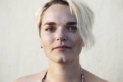 Portrait einer jungen Frau mit Grübchen und Sommersprossen