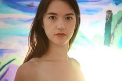 Gegenlichtportrait einer jungen Frau vor einer bunten Glaswand