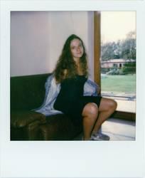 Polaroid: Junge Frau zieht ihre Jacke aus
