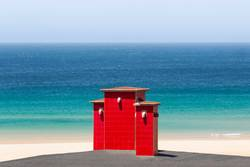 red roof chimneys in front of a deep blue sea