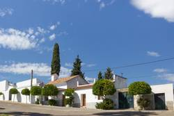 Typical Spanish house with white walls and cypress trees