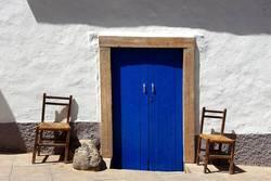 Blaue Tür und 2 Stühle an mediterraner weißer Hauswand