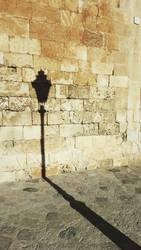Schatten von alter Straßenlaterne vor historischer Mauer