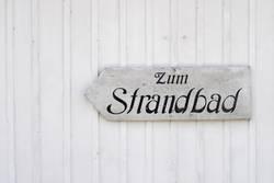 """Schild """"Zum Strandbad"""" auf weißer Holzwand"""