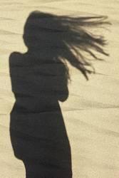 Schatten einer Frau mit langen Haaren am Strand