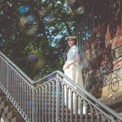 junge Frau steht auf Treppe u um sie herum toben dieSeifenblasen