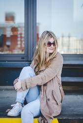 junge Frau mit Sonnenbrille sitzt auf Laderampe