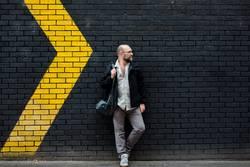 Mann vor einer schwarzen Wand mit gelben Pfeilen