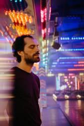 Mann mit geschlossenen Augen umgeben von künstlichem Licht
