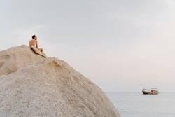 Mann mit freiem Oberkörper sitzt auf großem Fels am Meer