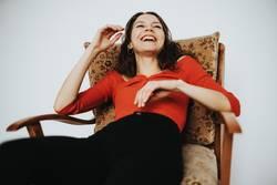 Frau sitzt im Sessel und lacht