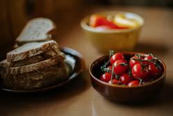 Teller mit Brotscheiben und Schüssel mit Kirschtomaten