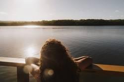 Junge Frau schaut vom Boot aus auf Mangrovenbucht