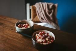 Zwei Schüsseln mit Haferflocken, Müsli und Weintrauben